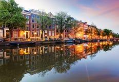 Västra sida för Amsterdam kanaler på skymning Natherlands arkivbild