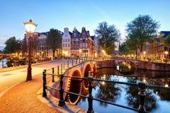 Västra sida för Amsterdam kanaler på skymning Natherlands royaltyfri foto