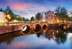 Västra sida för Amsterdam kanaler på skymning Natherlands, Europa royaltyfri foto