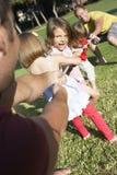 Väter und Kinder, die Tauziehen spielen Stockfotografie