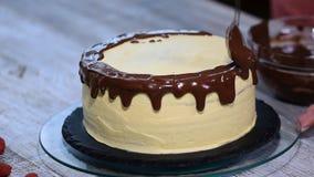 Vätskechoklad som häller på den nakna kakan stock video