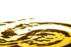 Vätskeguld- droppe och krusning Arkivfoto