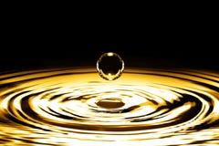 Vätskeguld- droppe och krusning Arkivbilder