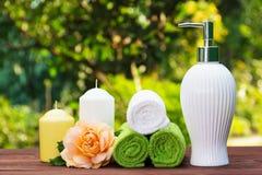 Vätsketvål, en bunt av handdukar, stearinljus och ett doftande steg Spa uppsättning för kroppomsorg Tvål-, handduk- och blommasno arkivfoton