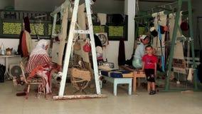 Väva för matta. Tre kvinna, Berber, matta-tillverkare. Väva fabriken i Tunisien stock video