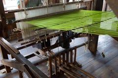 Väva grönt siden- tyg på vävstolen Fotografering för Bildbyråer
