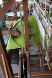 Väva grönt siden- tyg på vävstolen Arkivbilder