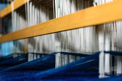 Väva vävstolen med blå vit ull i handling Royaltyfri Fotografi