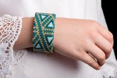Vävstolarmband på händer av unga flickan arkivfoton