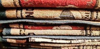 Vävt garn texturerade bakgrunden Kanter av etniska tappningmattor Hög av handgjorda asiatiska golvmats royaltyfri fotografi