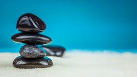 Växa travt upp av fyra svarta kiselstenar på ljus sand med blå bakgrund Fotografering för Bildbyråer