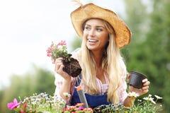 Växande blommor för kvinna utanför i sommar arkivbild