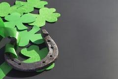 Växt av släktet Trifolium och hästsko på en mörk bakgrund Dag för St Patrick ` s Royaltyfri Bild