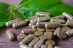 växt- drog i preventivpiller och kapsel på den wood tabellen Royaltyfria Bilder