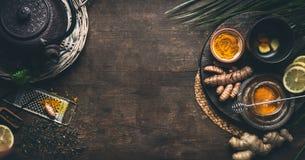Växt- gurkmejatebakgrund Kopp av sunt gurkmejakryddate med järntekannan och ingredienser: citron ingefära, kanelbruna pinnar royaltyfri bild