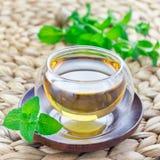 Växt- mintkaramellte i orientalisk glass kopp med ny pepparmint på bakgrund, fyrkantigt format Fotografering för Bildbyråer