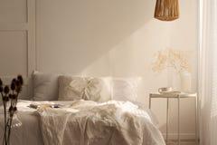Växt på tabellen bredvid säng med kuddar och ark i den vita enkla sovruminre arkivbild