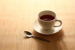 Växt- varmt te som lokaliseras i ett förlagt vitt exponeringsglas på ett trägolv royaltyfri foto