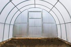 Växthus av polycarbonaten med fri jordning i försommar Royaltyfri Foto