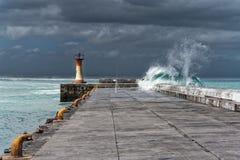 Våg över pir under storm, i Cape Town Sydafrika royaltyfri foto