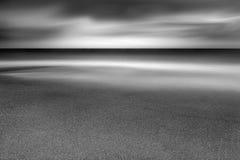 Våg över sand på den corniska stranden arkivbild