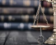 Våg av rättvisa och handbojor på en svart träbakgrund arkivfoto