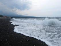 Våg-, bränning- och havsskum som slår den sandiga svarta vulkaniska sandstranden av Bali I Amed är havet tyst, men vågorna runt o fotografering för bildbyråer