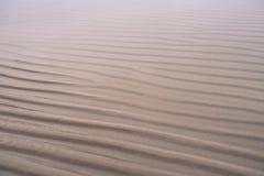 Våg-formad sand på stranden i vinter Arkivfoton