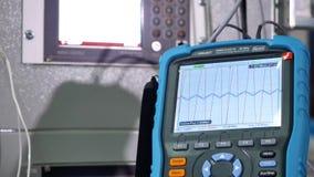 Våg på oscilloskopet Mannen skriver in värdena i oscilloskopet stock video