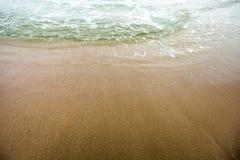 Våg på sandstranden Arkivfoto