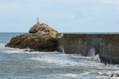 Våg som bryter på väggen av en hamn med en fyr på slutet och en molnig blå himmel arkivbilder