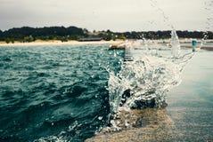 Våg som bryter på vågbrytaren med gröna metallpollare i Michig fotografering för bildbyråer