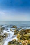 Våg som faller på den steniga stranden arkivbilder