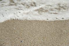 Våg som flyttar sig över sand royaltyfria foton