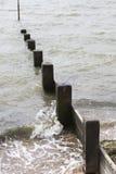 Våg som slår strandvågbrytare Arkivbilder