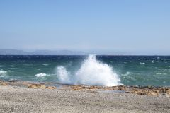 Vågen av medelhavet bryter på en stenig kust royaltyfri bild