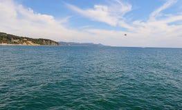 Vågen för himmel för havssommarvatten av den blåa semestern för stranden för bergsandkusten tränger igenom värme Arkivbild