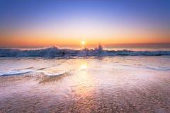 Vågen på stranden på solnedgången Royaltyfri Foto