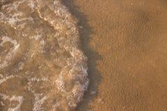 Vågen rullar på sanden arkivfoto