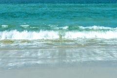Vågen skallr svepa på stranden royaltyfri foto