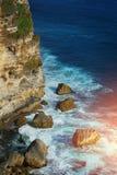 Vågen slår den stora stenUluwatu klippan, Bali Indonesien Royaltyfria Foton