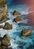 Vågen slår den stora stenUluwatu klippan, Bali Indonesien arkivbilder