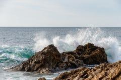 Vågen som bryter på, vaggar frånlands- i Laguna Beach, Kalifornien Arkivfoton