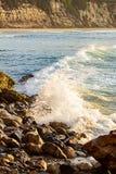 Vågen som bryter på, vaggar på shoreline med soluppgång royaltyfria bilder