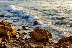 Vågen som bryter på, vaggar på shoreline på soluppgång arkivfoto