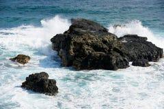 Vågen som ner bryter till färgstänk på kusten, vaggar på grisen-Gris, den Mauritius ön arkivfoton