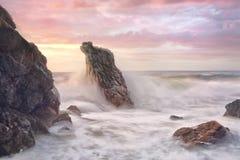 Vågen svaller till och med den steniga kustlinjen på soluppgång arkivfoto