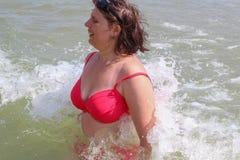 Vågen täcker kvinnan, kvinnan som spelar i havsvågorna Arkivbild