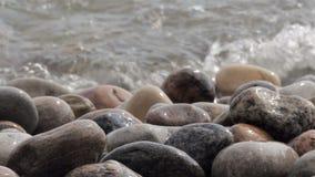 Vågkrasch över en stenig strand arkivfilmer
