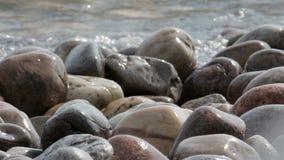 Vågkrasch över en stenig strand stock video